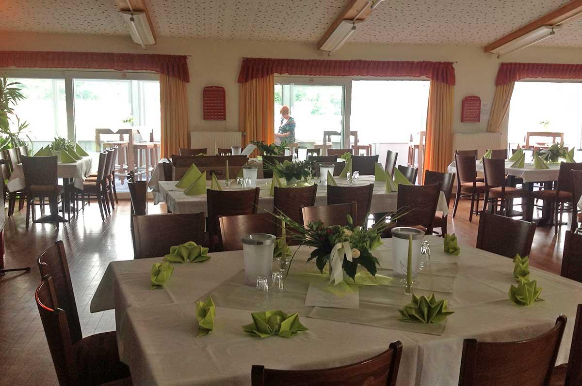 Gedeckte Tische im Hauptraum des Vereinsheims mit Blick in den Wintergarten